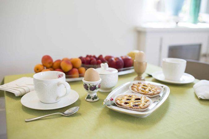 Colazione con latte, uova, crostate e frutta fresca